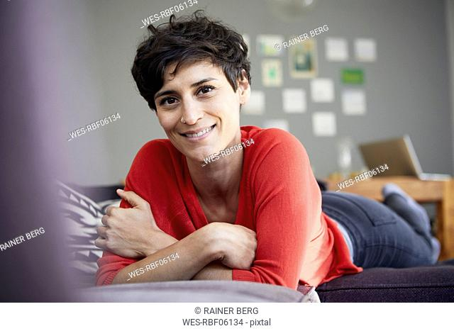 Portrait of smiling woman lying on couch at home