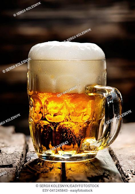Beer in mug on wooden table and dark background