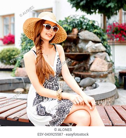 Stylish beautiful woman in summer clothes resting on a bench in the park