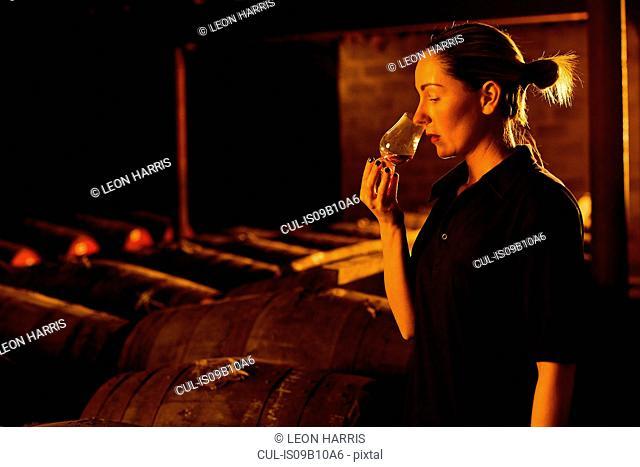 Female taster smelling whisky in glass at whisky distillery
