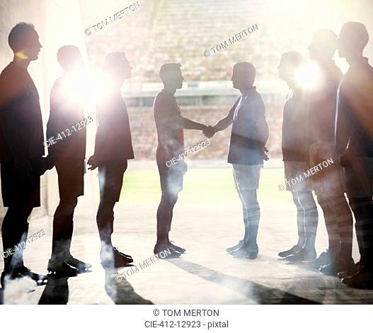 Silhouette of soccer teams shaking hands