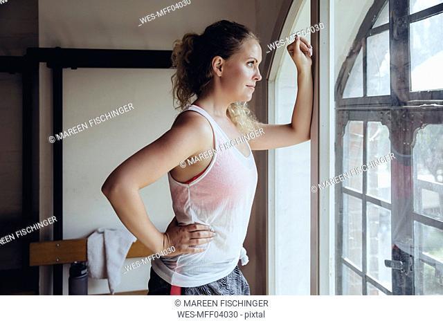 Woman standing in locker room looking out of window