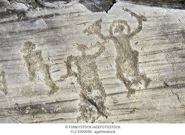 Petroglyph, rock carving, of two warriors one wearing a helmet and carrying a sword and shield. Carved by the ancient Camuni people in the iron age between...