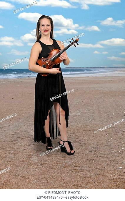 Beautiful young woman playing a violin classical instrument