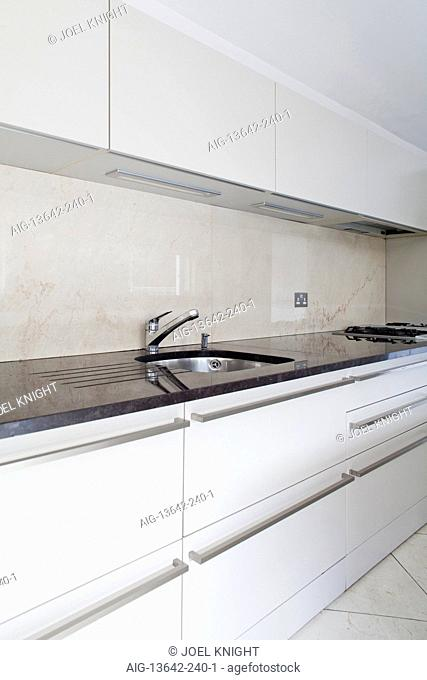 Detail of modern kitchen with white fitted units, London