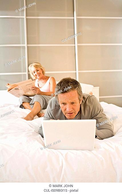 Couple on bed reading newspaper and using laptop