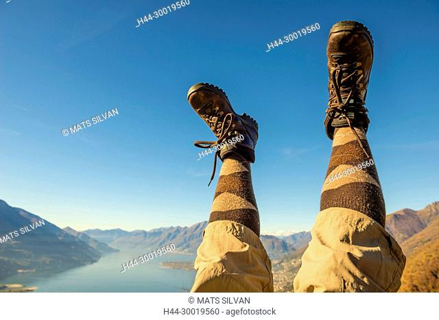 Hiking Shoes and Legs Up in the Air Over Alpine Mountain Range and Lake maggiore in Ticino, Switzerland