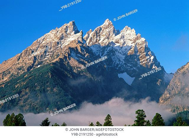 Sunrise on the Cathedral Group of the Teton Range with fresh autumn snow on peaks and valley fog; Grand Teton rises in the center, Grand Teton National Park