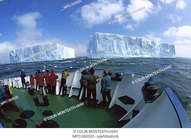 Tourists viewing large tabular icebergs from the deck of a boat, Southern Ocean, Antarctica