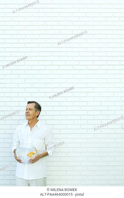 Man standing with eyes closed, holding goldfish bowl, in front of white brick wall, three quarter length