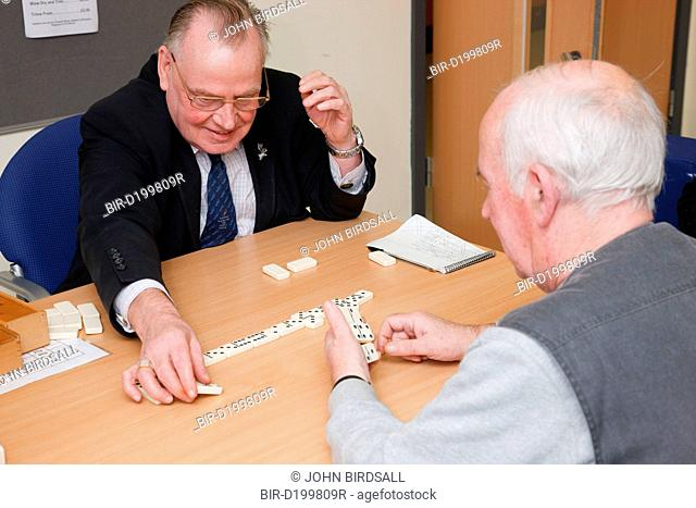 Volunteer playing dominoes with service user at a resource for people with physical and sensory impairment