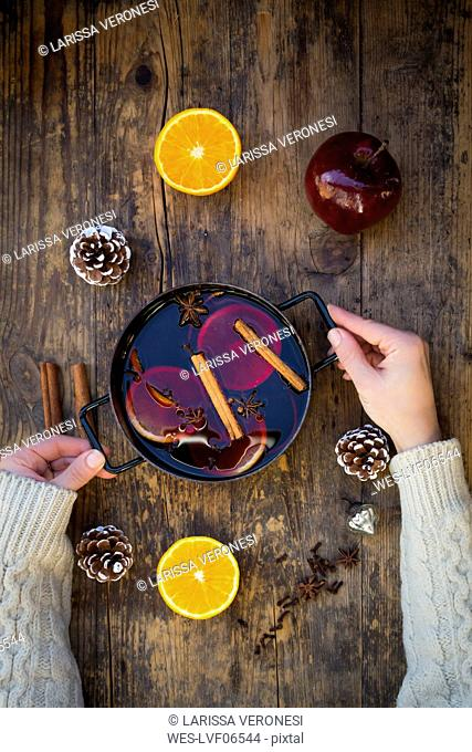 Woman's hands holding cooking pot of mulled wine with orange slices and spices