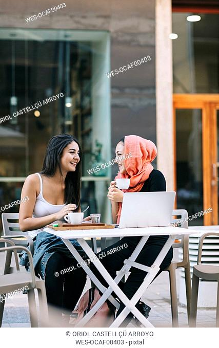 Two happy friends sitting together at a pavement cafe with laptop