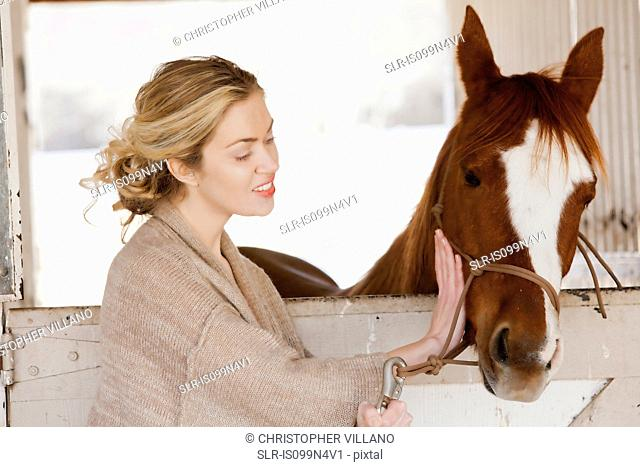 Young woman looking after horse in stable