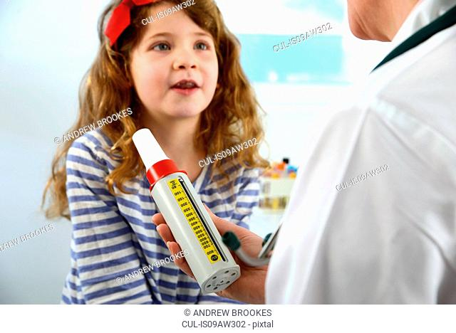 Girl about to breath into a peak flow meter (spirometer), lung function test