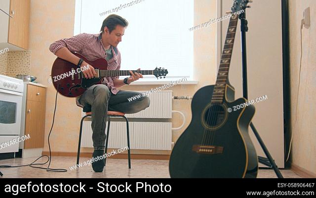 Young man musician composes music on the guitar and play in the kitchen, other musical instrument in the foreground, sitting