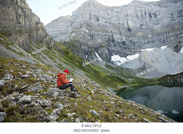 Woman writing in journal at remote mountain lakeside