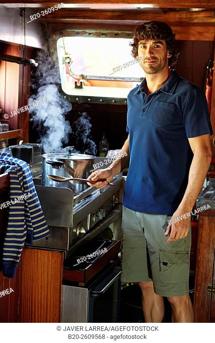 Young man in the kitchen of a sailboat, galleon. Basque Country. Spain