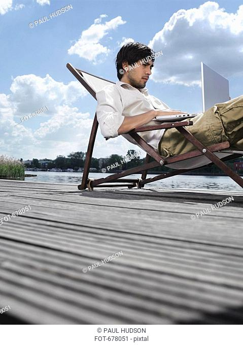 A young man sitting in a deck chair on a jetty using a laptop