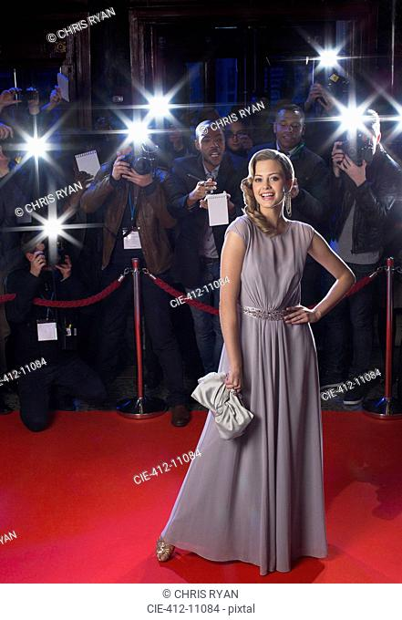 Portrait of well dressed female celebrity on red carpet with paparazzi in background