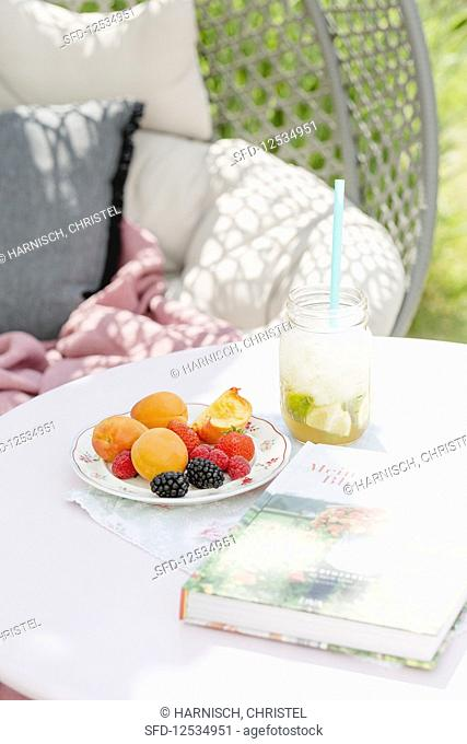 A fruit platter and virgin caipirinha cocktail on a garden table