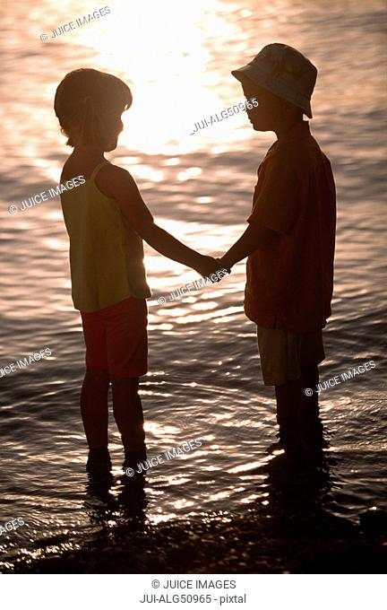 Silhouette of children holding hands at the beach