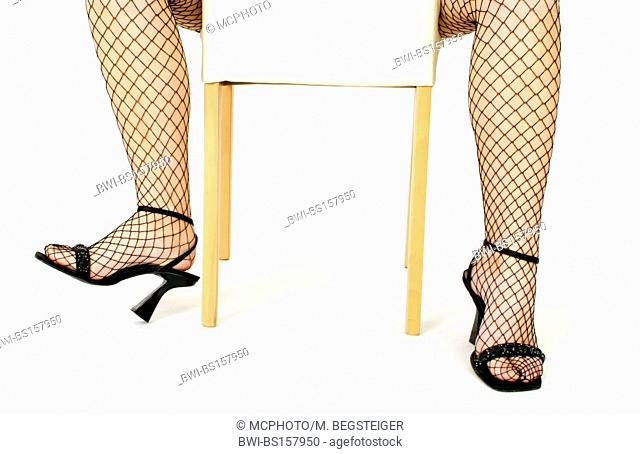 woman legs in fish-net stockings and high heels