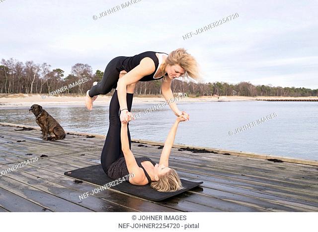Women exercising on pier