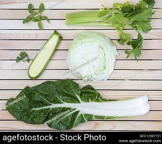 Flatlay of nutritious green herbs and vegetables arranged on a wooden background