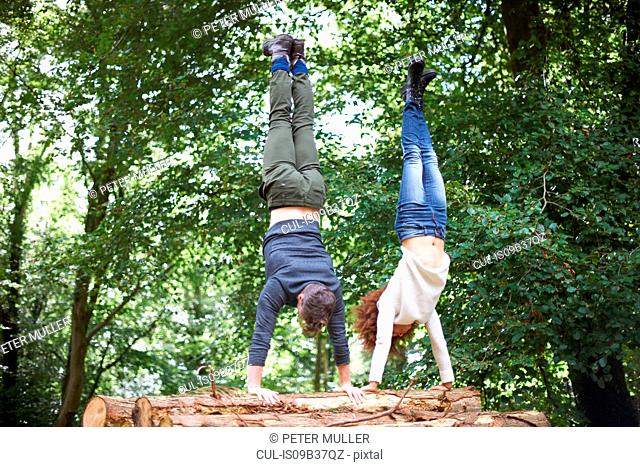 Couple in forest doing handstand on fallen tree