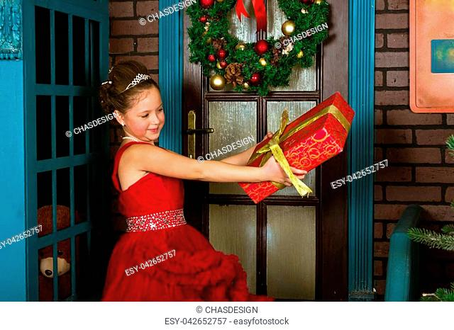 Little winter Princess in red dress with box-gift in hands welcomes New year and Christmas in enchanting holiday interior with decorated pine and Christmas...