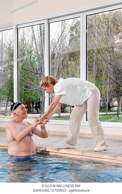 Health worker assisting a man in coming out from a swimming pool