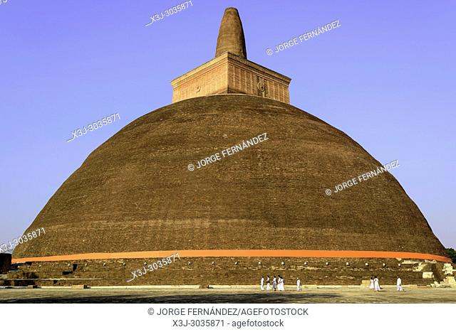 People walking around a stupa at Anuradhapura historical site. Sri Lanka