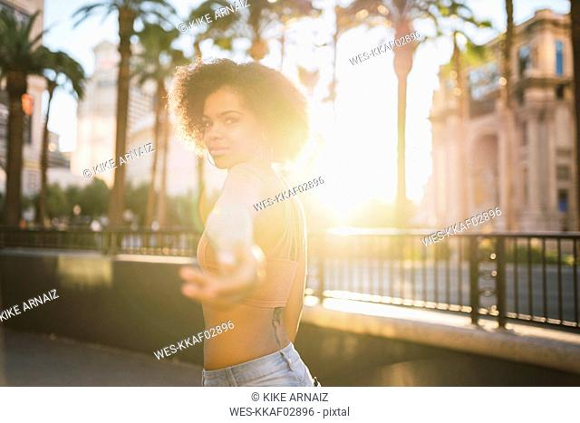 USA, Nevada, Las Vegas, portrait of young woman in the city in backlight