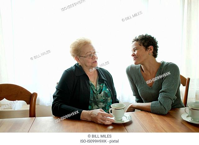 Mother and adult daughter sitting together over coffee