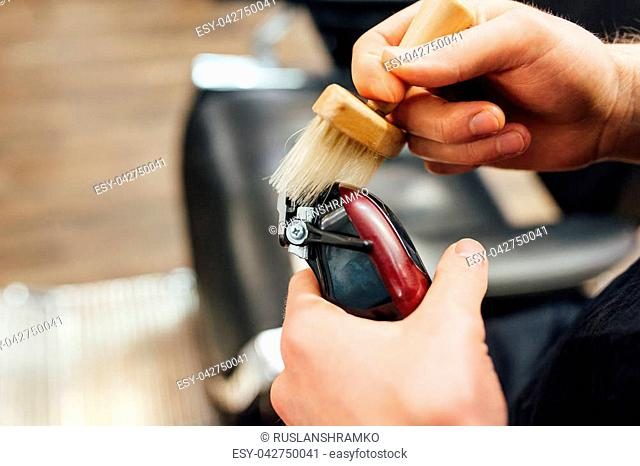 barber prepares for work electric trimmer. Uses a brush for cleaning tools