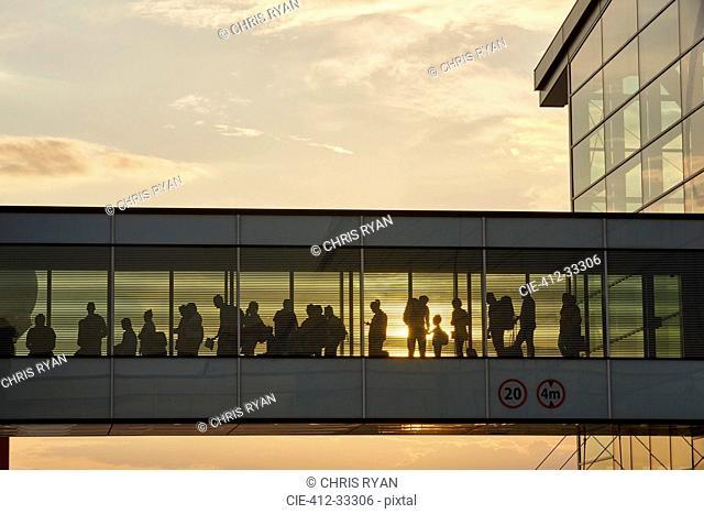 Silhouette people walking in airport sky bridge