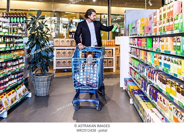 Girl sitting in cart while father shopping in supermarket