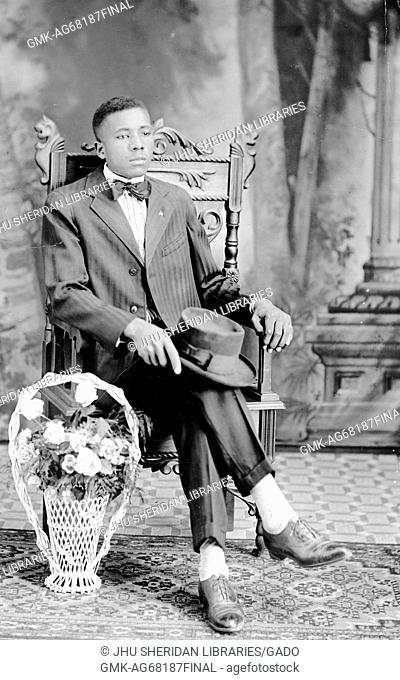 Full portrait of seated African American man, legs crossed, wearing a suit, with a hat on his lap, a flower bouquet next to his chair