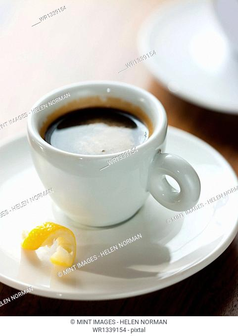 A cup of black coffee in a white china cup with a small twist of lemon peel in the saucer