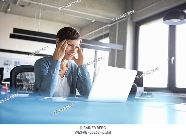 Businesswoman in office with head in hands using laptop