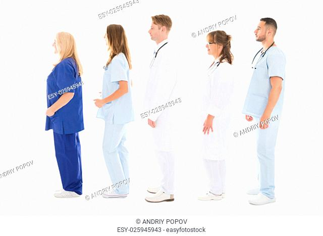 Full length side view of medical professionals standing in row against white background