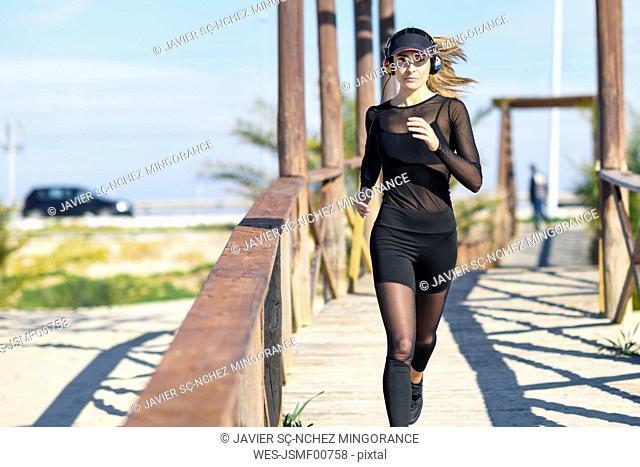 Sportive woman running on wooden bridge