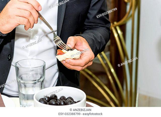 Businessman picking finger food at event. Black olives appetizer