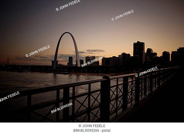 Arch landmark next to urban river at sunset