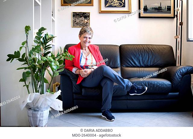 A woman posing sitting on a sofa with crossed legs. Livorno (Italy) 23rd August 2014