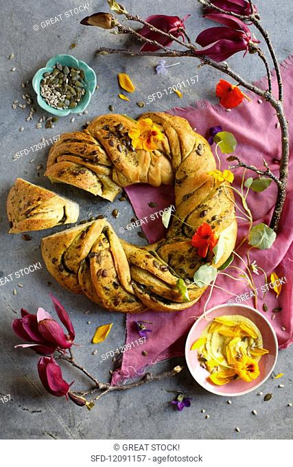 A bread ring with pumpkin seeds and nasturtium flowers