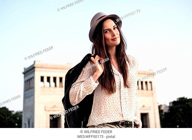 Portrait of young woman with long brown hair wearing hat, Munich, Germany