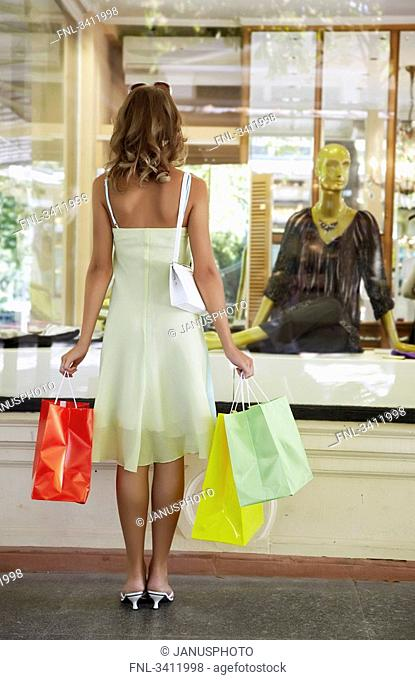 Young woman standing with shopping bags in front of a shop window