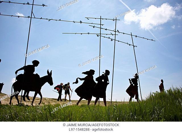 Two pilgrims walk past metal sculpture silhouettes of pilgrims on the Camino de Santiago, near Pamplona, Spain